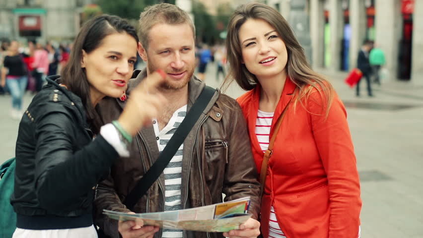 Happy tourist friends looking at map, guide in the city