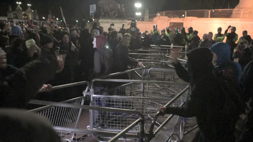 LONDON, UK - NOV 5: Protesters wearing Guy Fawkes masks shake railings during the Million Masks march on Bonfire night in London on November 5, 2014