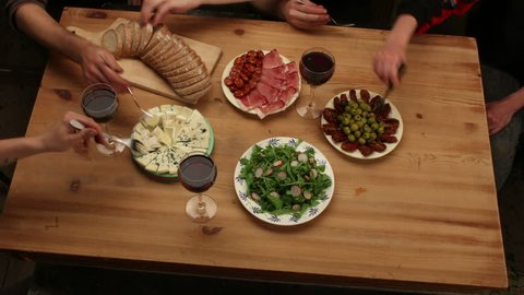 Preparing and eating food on wooden table with friends (antipasto, bread, salad, ham, cheese, olives, dried tomatoes...), 4K, top view