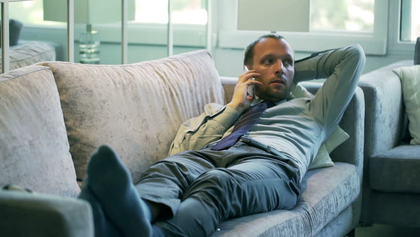 dfeb660fad Businessman lying on the couch and talking on cellphone. O. By OMNIS PL. Stock  footage ID  7913134. Video clip ...