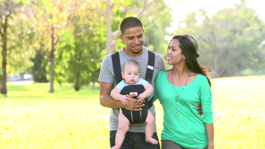 Slow motion sequence of parents with baby son in carrier walking towards camera through park. Shot on Sony FS700 at frame rate of 100fps | Shutterstock HD Video #7917304