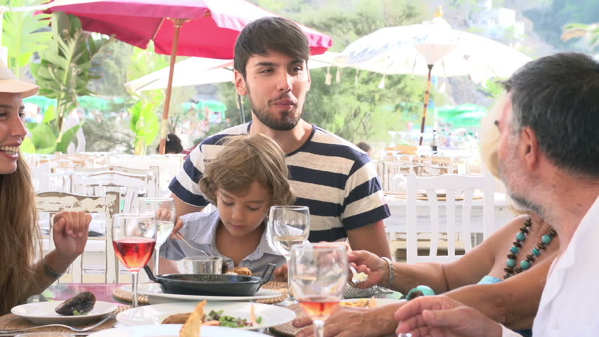 Camera tracks around table as multi-generation family enjoy meal around restaurant table. Shot on Sony FS700 at a frame rate of 25fps