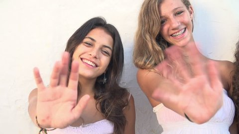 Slow motion sequence of three teenage girls smiling at camera and waving. Shot on Sony FS700 at a frame rate of 100fps