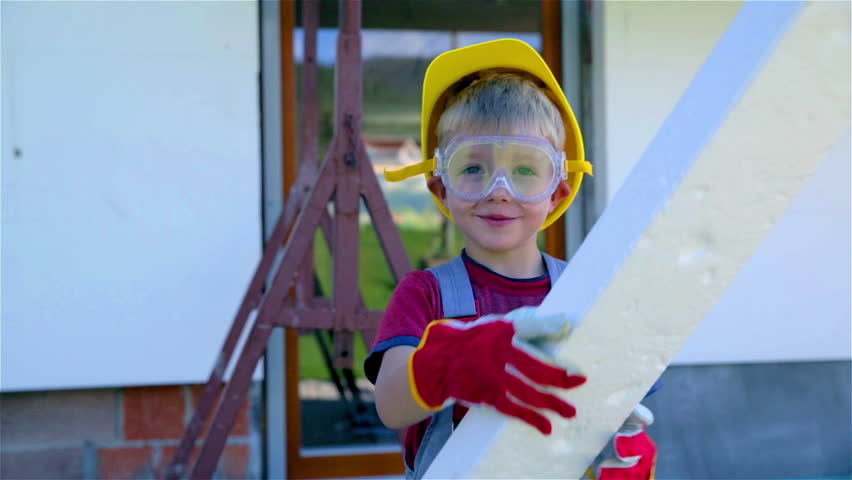 Child worker playing with styrofoam as sword. Jib wide lens shot of very young worker with protective helmet and glasses and gloves posing in front of house being protected against moist.