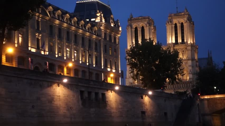 Notre Dame Cathedral in Paris at night, filmed from a cruise boat on the Seine River.