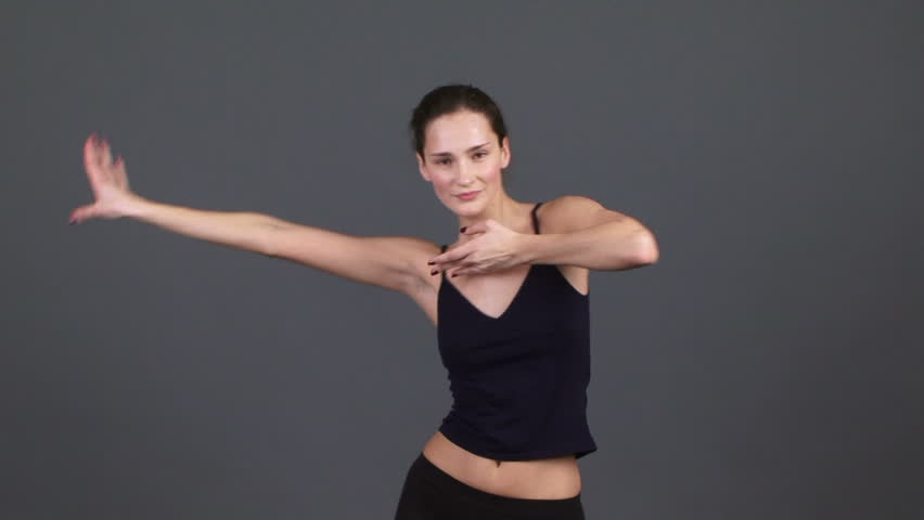 Artistic dancer. A beautiful girl dressed in black artistic dancing on a gray background.