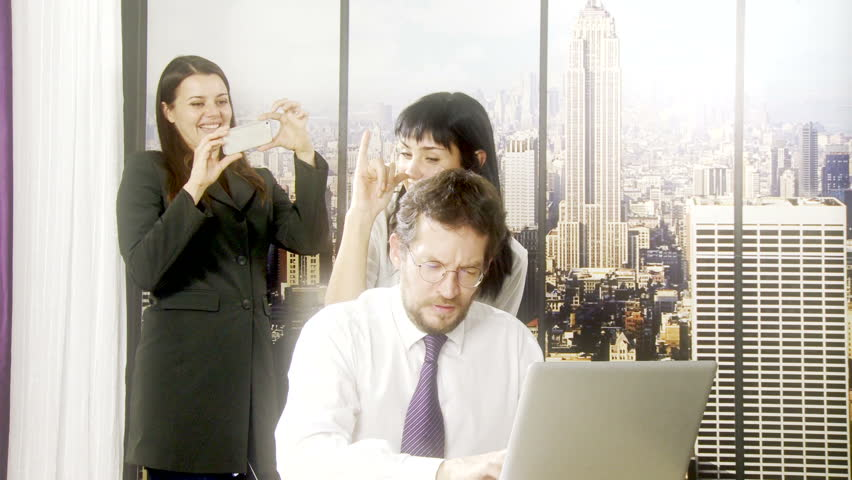 Two women in office teasing man working with computer #7988944