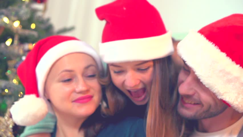 Young beauty teenage daughter presenting a surprise gift box to her parents. Giving presents. Emotions and family values. Christmas, Happy New Year celebration. HD video footage 1920x1080p. Slowmo    Shutterstock HD Video #8009884