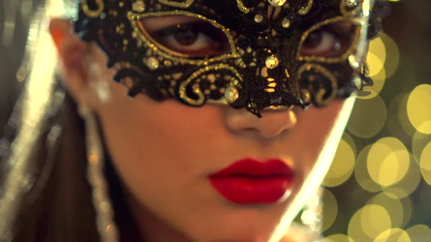 Sexy woman wearing venetian masquerade carnival mask at party, over holiday glowing background. Holiday make up and accessories. HD 1080p, slow motion 240 fps, high speed camera shot