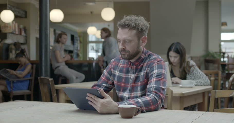 Man using tablet and drinking coffee in pub | Shutterstock HD Video #8044384