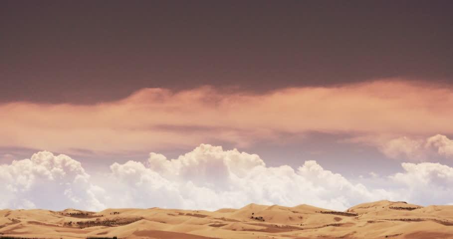 4k timelapse large white puffy cloud mass rolling over desert sand dunes under sunset glow.  gh2_08639_4k