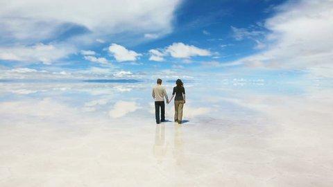 Man and woman walking away on the lake Salar de Uyuni, Bolivia
