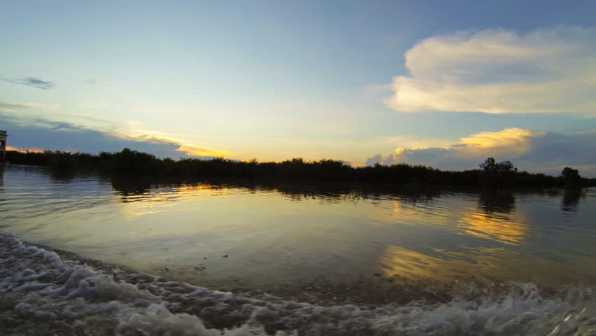 Boat passing near  Kampong plunk floating village at sunset in Tonle Sap lake in Cambodia recorded at slow motion 60fps