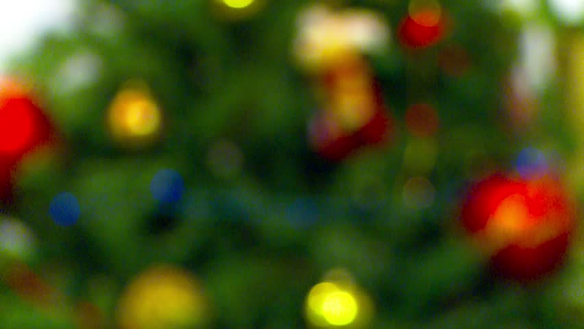 christmas candles flicker alongside christmas bells and greenery with white christmas lights in the soft focused background merry christmas