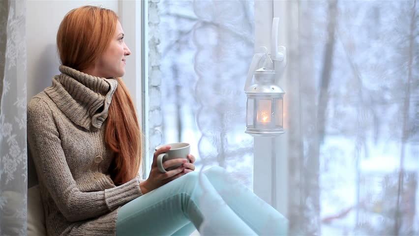 Young red-haired woman sitting on the windowsill, looking the window and drinking tea. Winter outside.