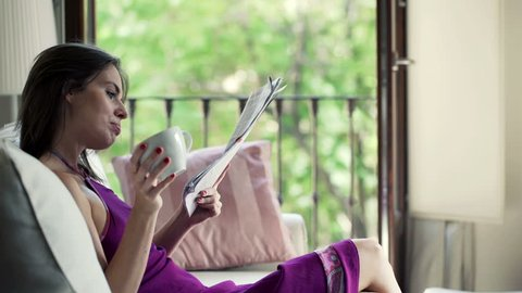 Young, pretty woman drinking coffee and reading magazine on sofa at home