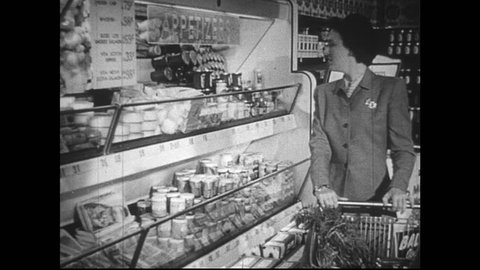 UNITED STATES 1950s : Housewife shopping for groceries at supermaket. A woman's hand selects bacon and milk. Housewife at supermarket checkout. She counts out money as cashier rings up groceries