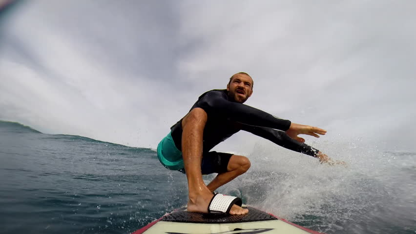 A surfer riding on small waves, maintains balance while riding, POV | Shutterstock HD Video #8258695