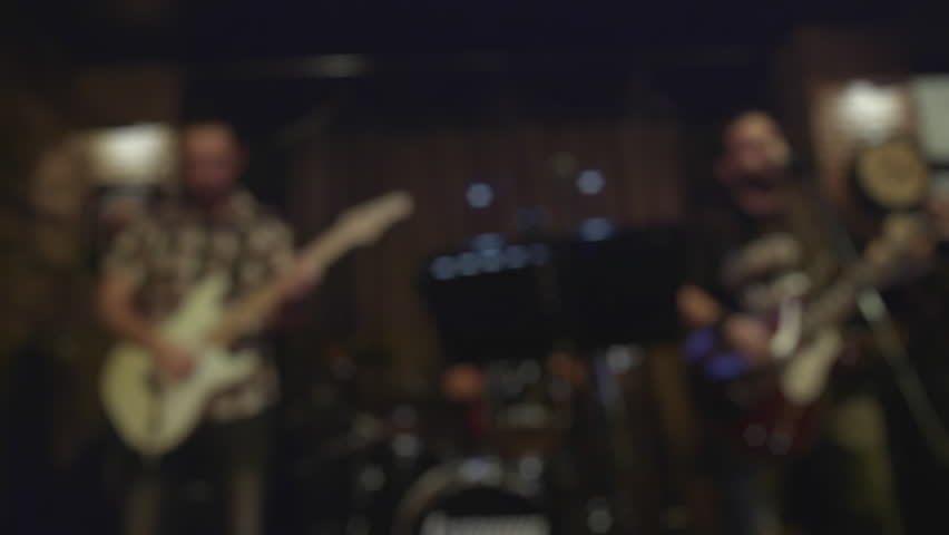 Guitar player  bassist and drummer performing instrumental live solo at a night music bar.Wide establishing shot out of focus.