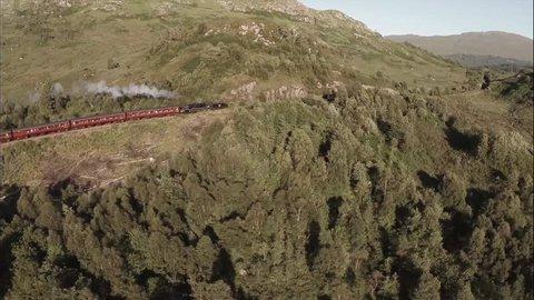 GLENFINNAN, SCOTLAND - JUNE 2014: Aerial shot of the Jacobite Steam Train going through stunning scenary in the Scottish highlands