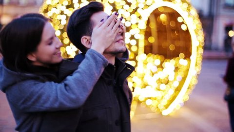 Young woman surprises his boyfriend by covering his eyes in city during evening