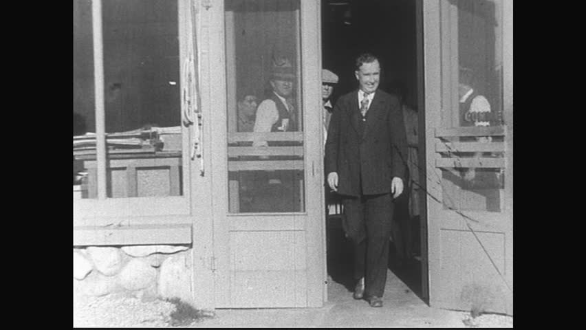 CALIFORNIA- CIRCA 1929: A woman and several men exit a business at the same time.  A car pulls out of a parking lot; several young paper boys follow it on their bikes.
