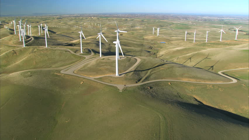 Low aerial view of cluster of wind turbines in green hillside