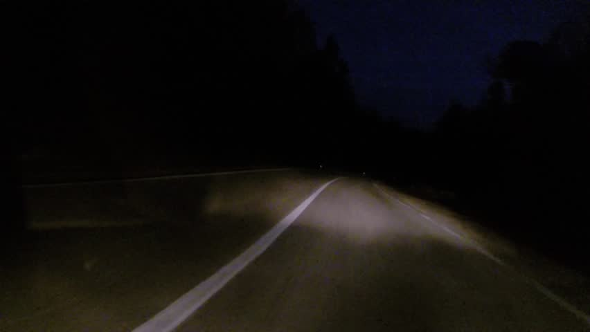 Car driving at night on country road