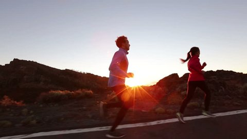 Running sport athletes woman and man jogging at night sunset. Runners training exercising on road in beautiful mountain landscape. Healthy lifestyle concept.