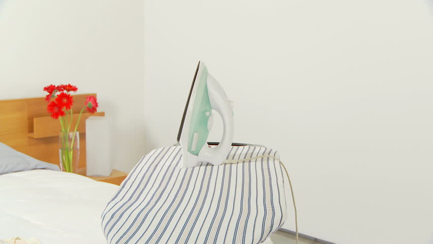 Young woman ironing clothes in a hurry