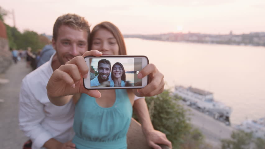 Couple taking selfie self portrait in Stockholm. Candid fresh Scandinavian man and Asian woman looking at old town cityscape sunset view from Monteliusvagen overlooking Gamla Stan, the old city. | Shutterstock HD Video #8454994