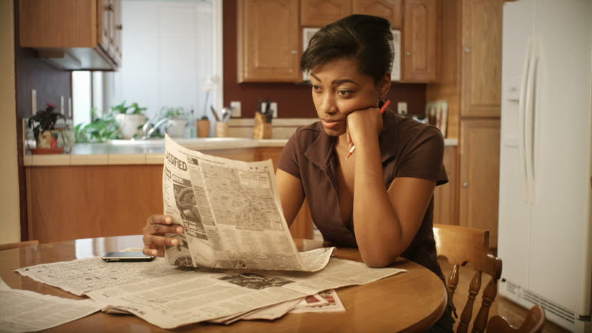 An African American woman performs various tasks around the house.