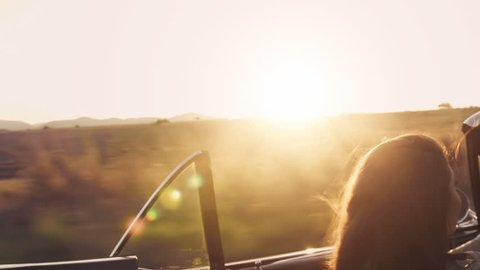 Close up of a couple driving classic cherry red convertible, cabriolet car, at sunset with sun flare. Steadicam shot.