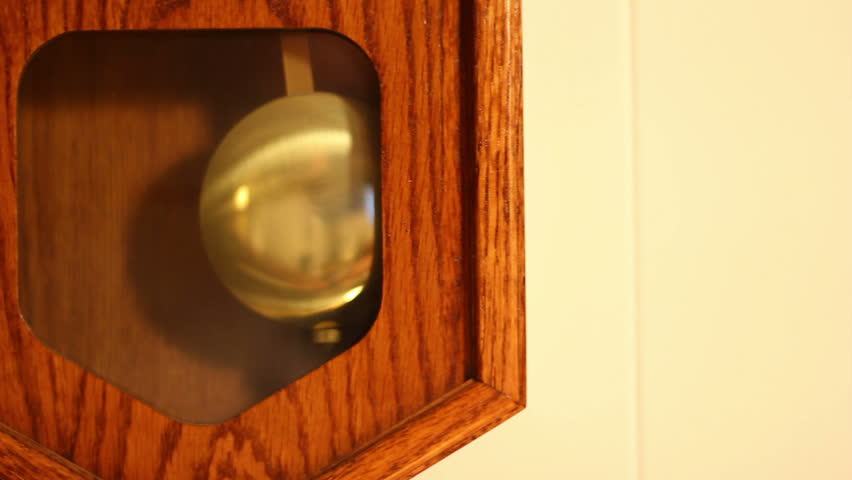 Close-up of the pendulum of a household wall clock.