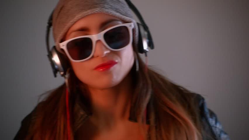 Young pretty Latino woman listening to Hip Hop music thorough headphones | Shutterstock HD Video #8535829