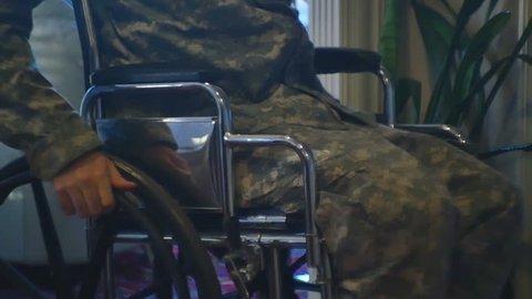 A veteran in camo moving in a wheelchair