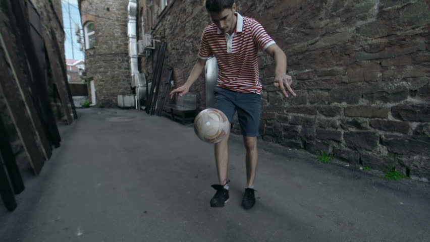 Pan shot of soccer player tossing the ball and catching with his back