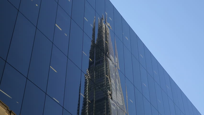 the shard London reflecting in tall building next to the shard at London Bridge Station #8570941
