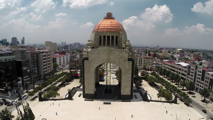 General aerial shot of the Monumento a la Revolucion, surrounded by lots of buildings in a panoramic view of Mexico City