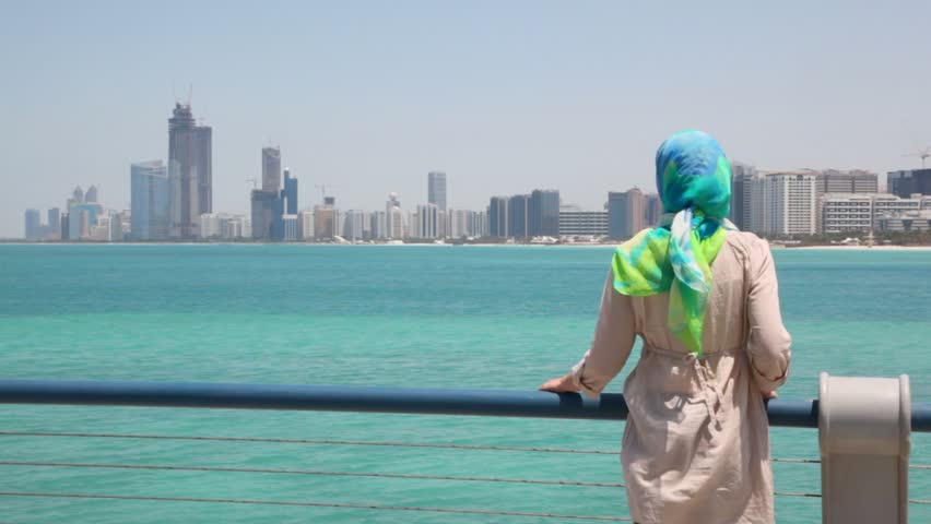 young woman stand on shore and looks at skyscrapers in Abu Dhabi, UAE