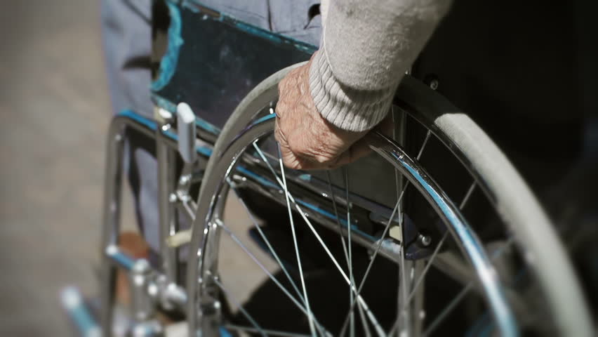 Tilt up of wheelchair details with cropped unrecognizable patient driving it