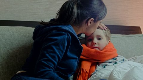 Young mother gives her sick son medicine in bed