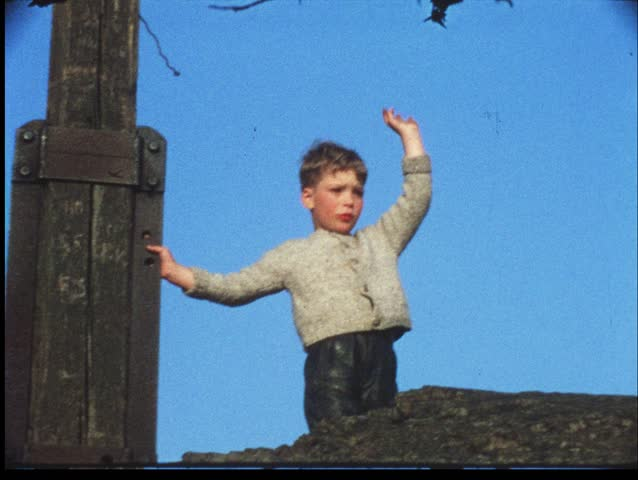 Boy waves goodbye from summit of mountain (vintage 8 mm amateur film)