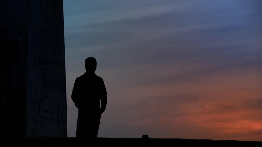 Thoughtful man standing towards sunset/sunrise. Full HD, 1080p, 1920x1080.