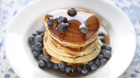 Delicious hot pancakes with fresh blueberries and natural maple syrup