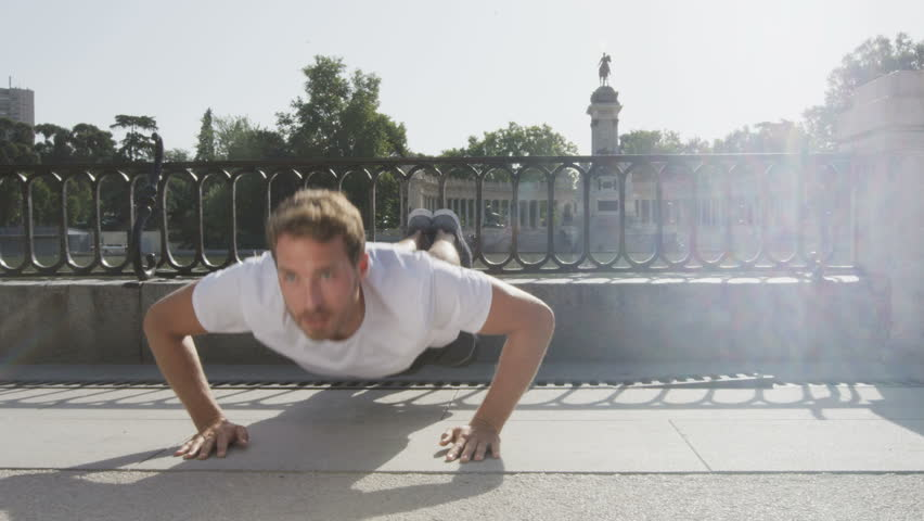 Athlete doing push-ups on run in park. Fitness guy exersicing training for healthy lifetyle in El Retiro Park, Madrid, Spain.
