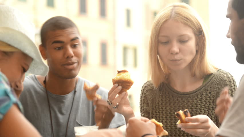 Four multiethnic friends have breakfast eating jam stuffed brioches in summer day - HD video footage