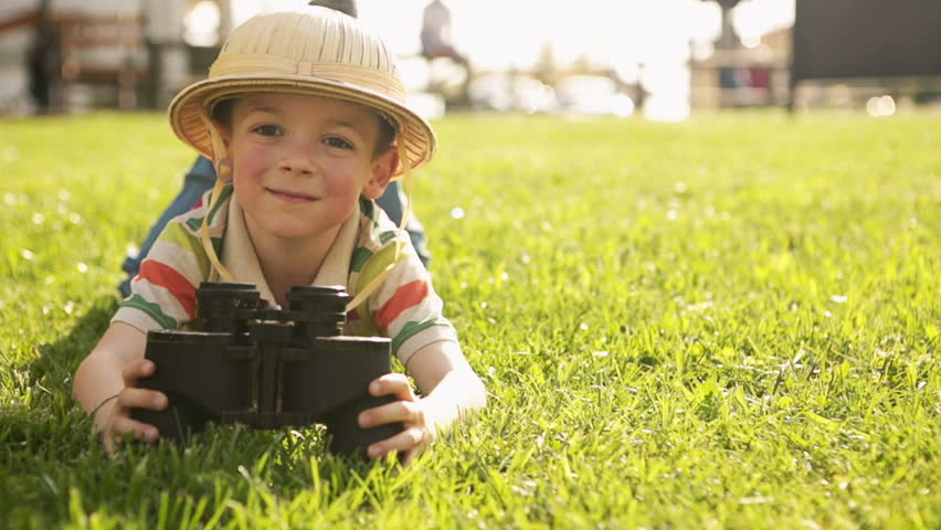 Child wearing pith helmet is playing in summer day with binoculars lying  down on the grass at town park - HD video footage 591bcae41d4
