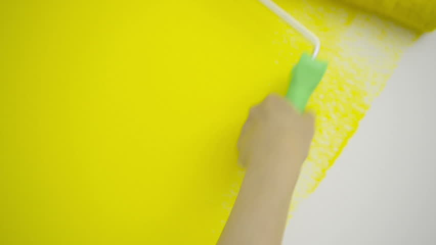 Young Woman Is Painting With Paint Roller A White Wall With Yellow ...