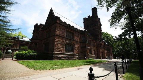 PRINCETON, NJ/USA - JUNE 20, 2014: Family walks near a historic stone building on Princeton University campus.